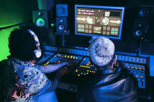 Músico e engenheiro de som mixando novo álbum em estúdio de gravação boutique - foco suave em fones de ouvido masculinos