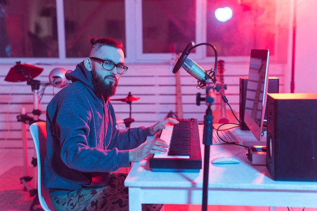 Músico e fazendo música conceito - produtor de som masculino trabalhando em estúdio de gravação.