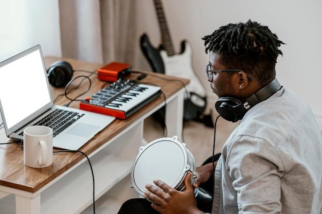 Músico em casa tocando bateria e mixando com laptop