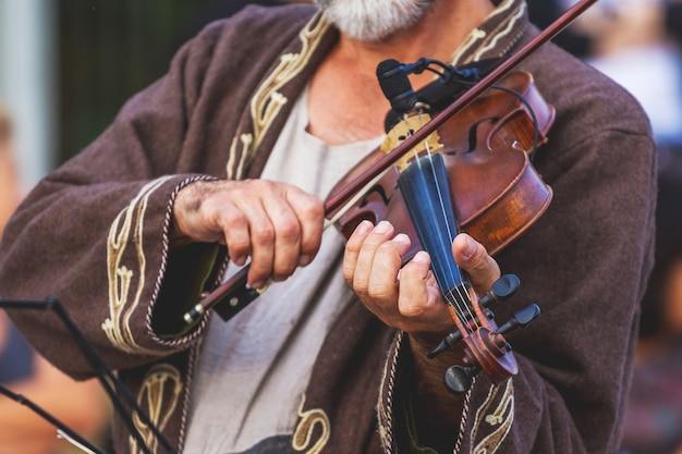 Músico em vestido vintage com um violino enquanto tocava em um show_