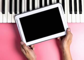 Músico está segurando a tela do tablet em branco para aplicação de música simulada