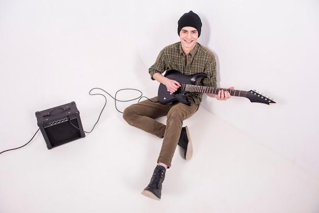 Músico está tocando um baixo de seis cordas no estúdio.