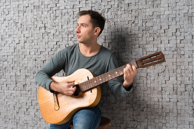 Músico homem dentro de casa tocando violão clássico