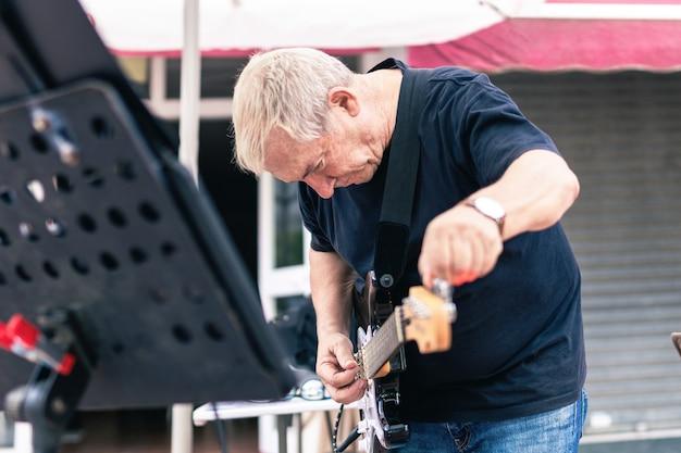 Músico idoso afinando sua guitarra elétrica no palco