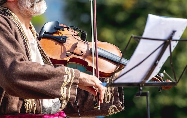 Músico idoso com um violino na rua perto de uma mesa de música com notas_