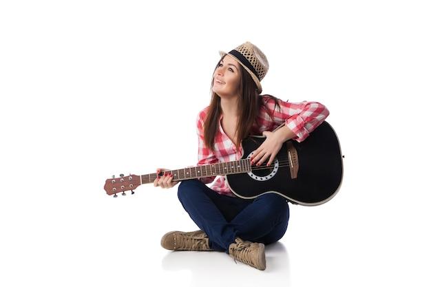 Músico jovem com guitarra, vestindo camisa e chapéu, sentado no chão e sorrindo. fundo branco.