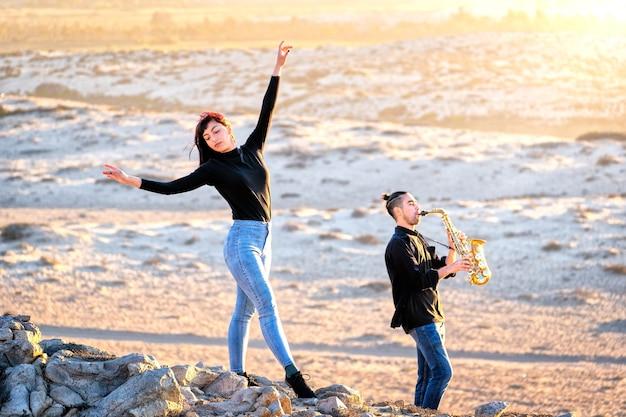 Músico latino está tocando saxofone enquanto uma mulher latina dança na paisagem do deserto