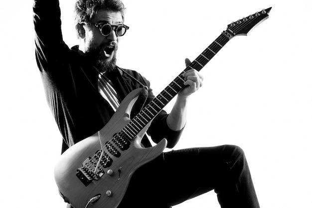 Músico masculino com luz de fundo de guitarra de rock star. foto de alta qualidade