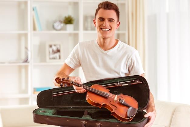 Músico masculino novo com um violino que senta-se no sofá.