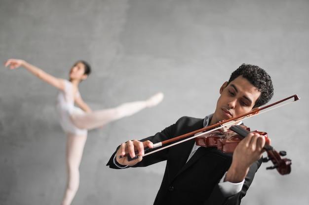 Músico masculino toca violino enquanto dança desfocada bailarina