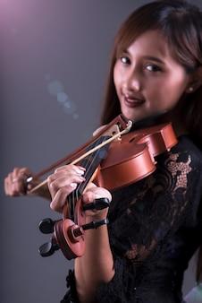 Músico menina tocar violino no fundo escuro, close-up