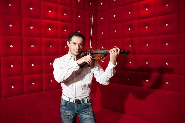 Músico novo que joga o violino em um restaurante em uma parede vermelha.