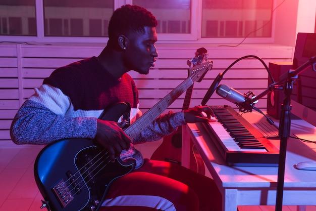 Músico profissional afro-americano gravando baixo em estúdio digital em casa, conceito de tecnologia de produção musical.