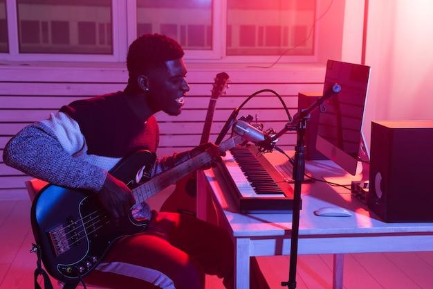 Músico profissional afro-americano gravando baixo em estúdio digital em casa, música