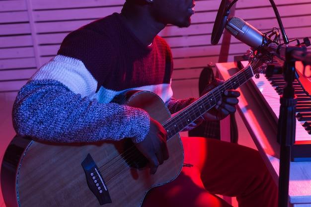 Músico profissional afro-americano gravando violão em estúdio digital em casa, produção musical