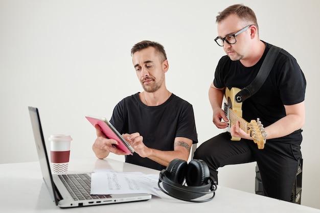 Músico seguindo notas no computador tablet