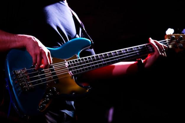 Músico segurando um baixo tocando um show em um bar noturno