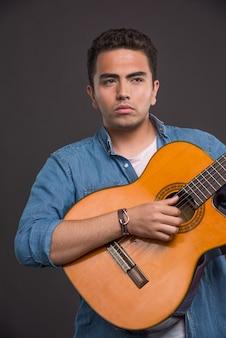 Músico sério tocando violão em fundo preto