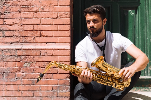 Músico sonhador posando com saxofone