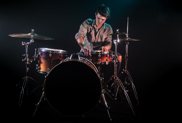 Músico tocando bateria, fundo preto e bela luz suave, jogo emocional, conceito de música