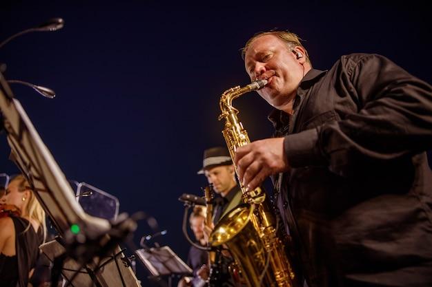 Músico tocando saxofone sob o céu azul da noite