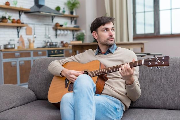 Músico tocando violão dentro de casa