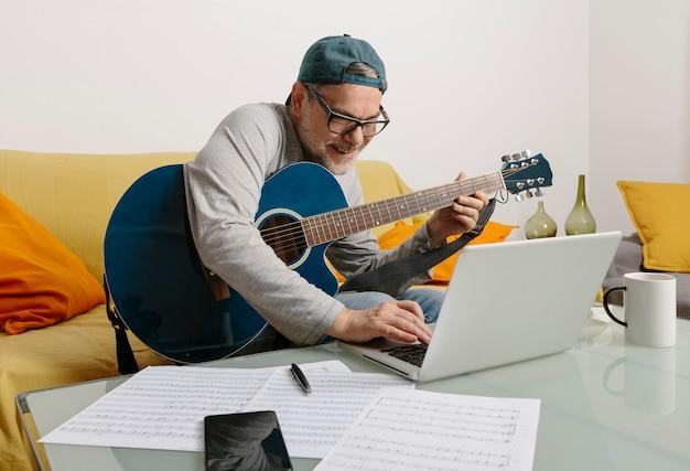 Músico tocando violão e compondo música com seus colegas por videoconferência em seu laptop