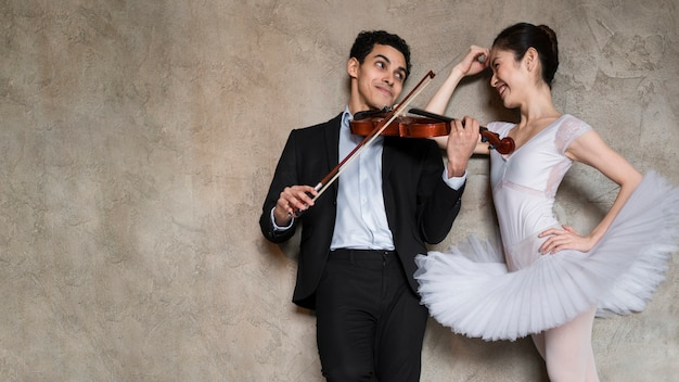 Músico tocando violino e bailarina ouvindo