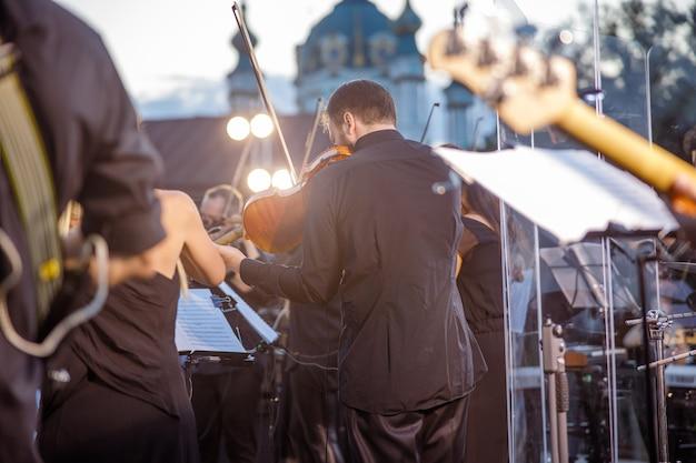 Músico tocando violino em show ao ar livre