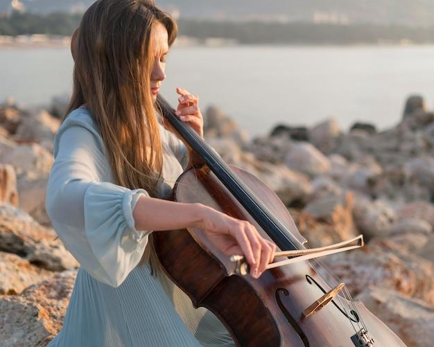 Músico tocando violoncelo ao pôr do sol nas rochas