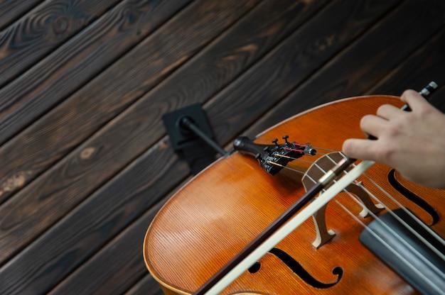 Músico tocando violoncelo no chão de madeira