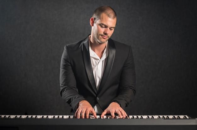 Músico vestido de maneira elegante tocando teclado e olhando para o instrumento