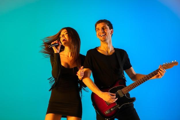 Músicos, cantores e guitarristas caucasianos, isolados no fundo azul do estúdio em luz de néon