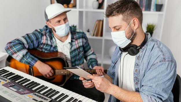 Músicos de tiro médio usando máscaras de proteção