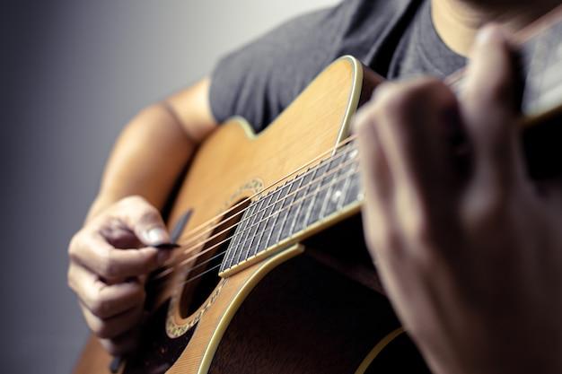 Músicos do sexo masculino seguram acordes e dedilham o violão.