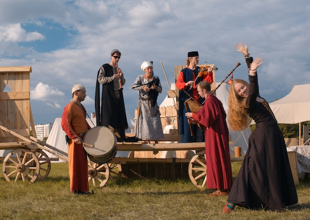 Músicos folclóricos e dançarina mulher.