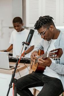 Músicos masculinos em casa tocando violão e teclado elétrico