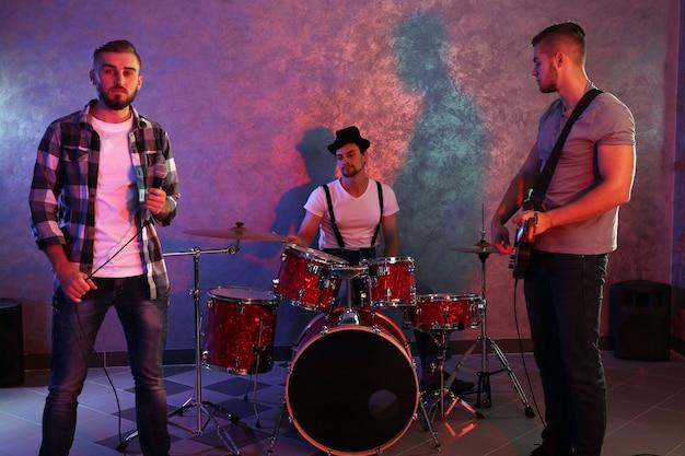 Músicos tocando instrumentos musicais e cantando canções em um estúdio