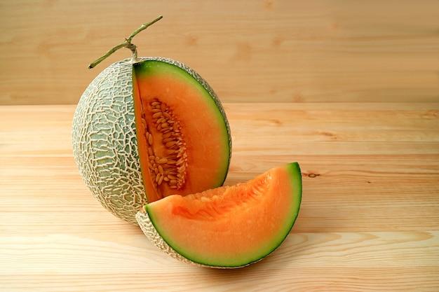 Muskmelon fresco maduro de cor laranja com uma fatia de fruta inteira