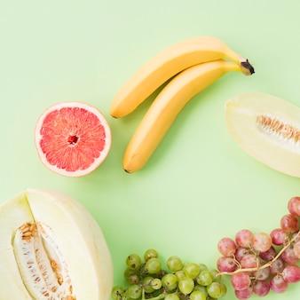 Muskmelon; toranja cortada ao meio; banana; uvas vermelhas e verdes em fundo colorido