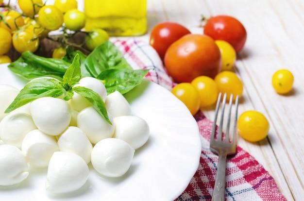 Mussarela fresca com tomate amarelo e manjericão.