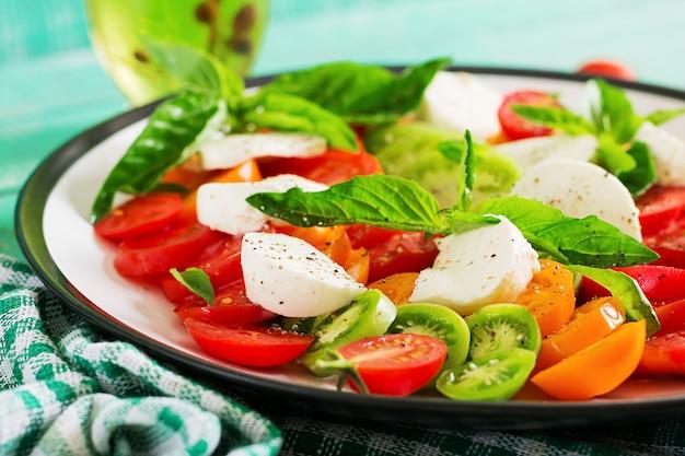 Mussarela, tomate e manjericão erva folhas no prato sobre a mesa de madeira branca. salada caprese. comida italiana.