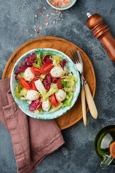 Mussarela, tomate e mistura de folhas frescas de salada, fundo escuro, vista superior. brincar.
