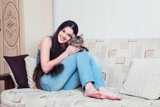 Ñ mulher jovem e bonita abraçando um gato em casa