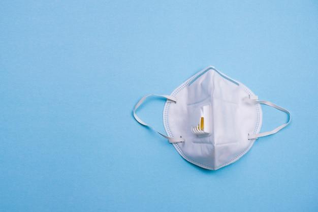 N95 ou máscara cirúrgica branca sobre fundo azul.