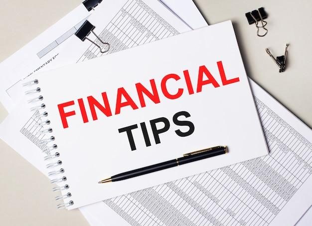 Na área de trabalho encontram-se documentos, caneta, clipes pretos e um caderno com o texto dicas financeiras. conceito de negócios