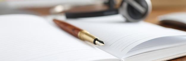 Na área de trabalho está o diário com caneta e fones de ouvido, trabalho remoto pelo conceito do operador