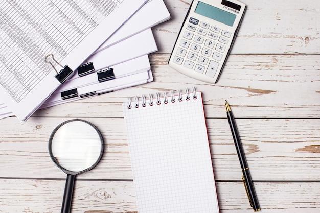 Na área de trabalho estão óculos, uma calculadora, uma lupa, uma caneta e um caderno em branco com local para inserir texto
