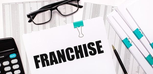 Na área de trabalho estão relatórios, documentos, óculos, calculadora, caneta e papel com o texto franquia. conceito de negócios