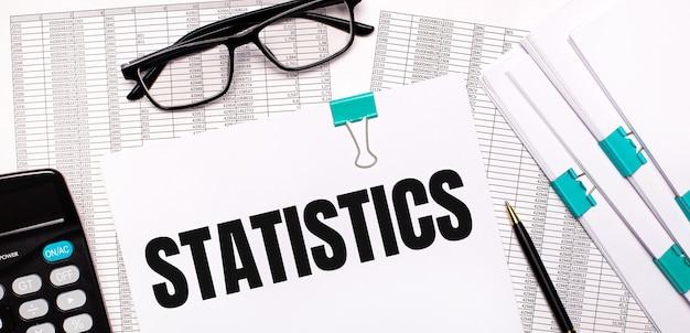 Na área de trabalho estão relatórios, documentos, óculos, uma calculadora, uma caneta e um papel com o texto estatísticas. conceito de negócios